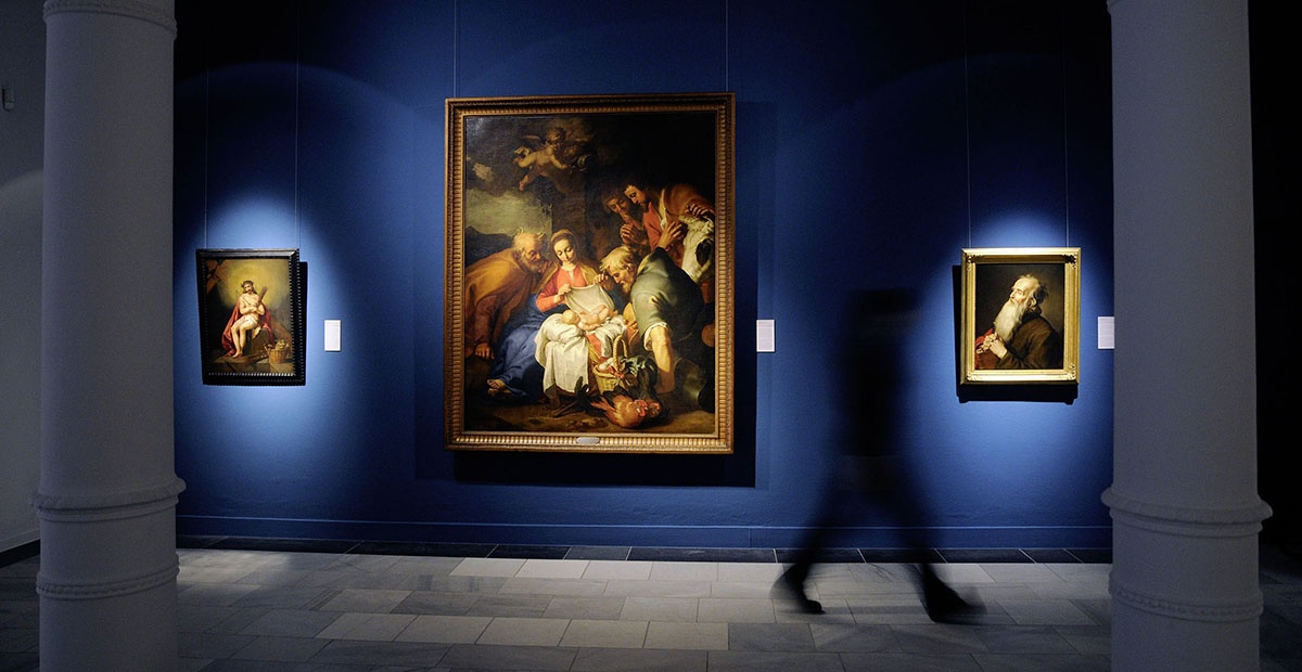 State Museum Schwerin: dark room with three lit paintings in front of a blue wall